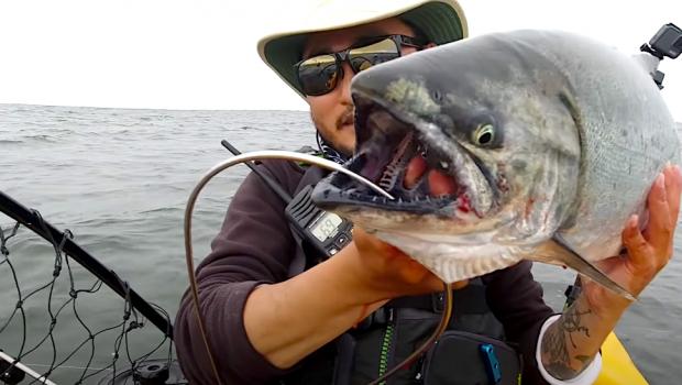 Taku Kondo holding a king salmon kayak fishing in the pacific ocean